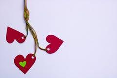 3 сердца соединили красочные веревочки - на белой предпосылке, космосе экземпляра Стоковое Изображение