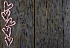 Сердца тросточки конфеты на деревенской древесине стоковая фотография