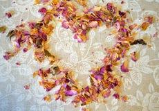 Сердце высушенных лепестков чая подняло на скатерть с белыми розами и место для вашего текста Стоковое Изображение
