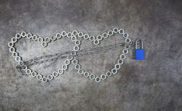 Сердце 2 гаек с голубым ключом на предпосылке металла Hea гайки Стоковое Изображение