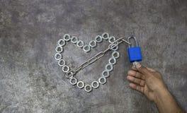 Сердце гайки с голубым ключом на предпосылке металла Hea гайки стоковые фото