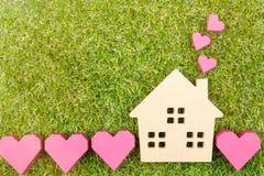 Сердце деревянной игрушки дома и бумажной коробки красное формирует на земном зеленом цвете g Стоковое Изображение RF