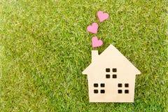 Сердце деревянной игрушки дома и бумажной коробки красное формирует на земном зеленом цвете g Стоковое Фото
