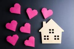 Сердце деревянной игрушки дома и бумажной коробки красное формирует на черном backgrou Стоковое фото RF