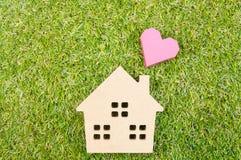 Сердце деревянной игрушки дома и бумажной коробки красное формирует на земном зеленом цвете g Стоковые Фотографии RF