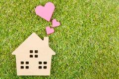 Сердце деревянной игрушки дома и бумажной коробки красное формирует на земном зеленом цвете g Стоковые Изображения