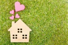 Сердце деревянной игрушки дома и бумажной коробки красное формирует на земном зеленом цвете g Стоковое Изображение