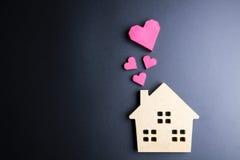 Сердце деревянной игрушки дома и бумажной коробки красное формирует на черном backgrou Стоковые Фотографии RF