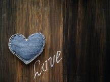 Сердце джинсовой ткани и ВЛЮБЛЕННОСТЬ надписи Стоковые Фото