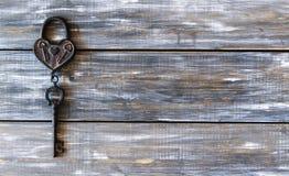 Сердце и ключ на деревянной предпосылке Стоковая Фотография RF
