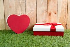 Сердце и присутствующая коробка на зеленой траве Стоковое Фото