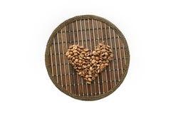 Сердце кофейных зерен на круглой рогожке Стоковые Фотографии RF