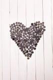 Сердце клало вне от кнопок на белый деревянный стол предпосылки Стоковые Фото
