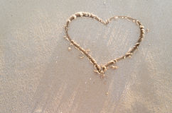 Сердце нарисованное на песке пляжа Стоковое Изображение