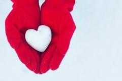 Сердце от снега в руках на предпосылке зимы Стоковые Изображения RF