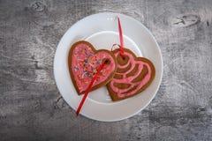 Сердце печений пряника шоколада сформировало с красной и розовой замороженностью на белой плите Стоковые Фотографии RF