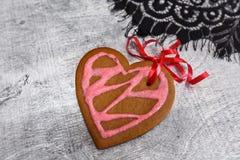Сердце печений пряника шоколада сформировало с красной и розовой замороженностью на белой плите Стоковое фото RF