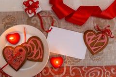 Сердце печений пряника шоколада сформировало с красной и розовой замороженностью и красной лентой затем на красочной ткани Стоковое Изображение RF