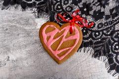 Сердце печений пряника шоколада сформировало с красной и розовой замороженностью на белой плите Стоковые Фото