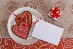 Сердце печений пряника шоколада сформировало с красной и розовой замороженностью и красной лентой затем на красочной ткани Стоковое Изображение