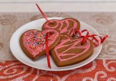 Сердце печений пряника шоколада сформировало с красной и розовой замороженностью на белой плите Стоковая Фотография