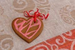 Сердце печений пряника шоколада сформировало с красной и розовой замороженностью и красной лентой на красочной ткани Стоковое Фото