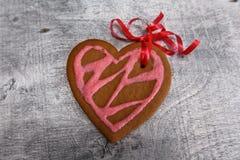 Сердце печений пряника шоколада сформировало с красной и розовой замороженностью на белой плите Стоковые Изображения RF