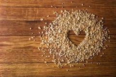 Сердце покрашенное в овсяной каше на деревянной предпосылке еда принципиальной схемы здоровая Стоковое Фото