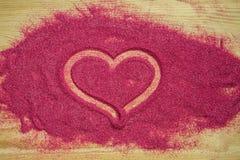 Сердце покрашенное на пинке покрасило песок с сусалью Стоковые Фото