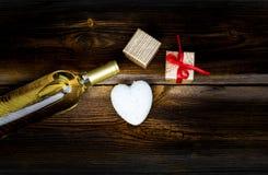 Сердце, подарки и бутылка вина на таблице Стоковые Изображения RF