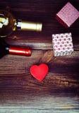 Сердце, подарки и бутылки вина на таблице Стоковая Фотография