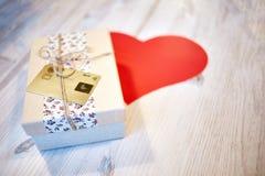 Сердце подарочной коробки и бумаги на деревянном столе Стоковое фото RF