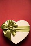 Сердце подарочной коробки с зеленым смычком на красной предпосылке Стоковые Фото