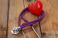Сердце при стетоскоп, изолированный на деревянной предпосылке Стоковые Фото