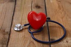 Сердце при стетоскоп, изолированный на деревянной предпосылке Стоковые Изображения