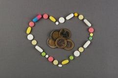 Сердце созданное от покрашенных пилюлек с деньгами МЕДИЦИНСКАЯ принципиальная схема Стоковая Фотография