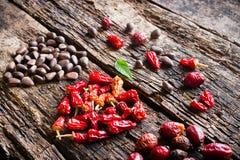 Сердце сухого красного перца, гаек сосны, dogrose на деревянном взгляде со стороны предпосылки Стоковые Изображения RF