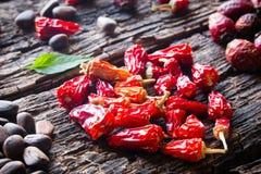 Сердце сухого красного перца, гаек сосны, dogrose на деревянном Стоковое Изображение