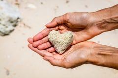 Сердце сформировало коралл в руках, остров Boracay, Филиппины Стоковая Фотография