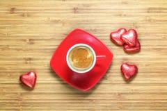 Сердце сформировало помадки обернутые в яркой красной фольге лежа на деревянной текстуре с красной чашкой coffe около его Стоковое Изображение