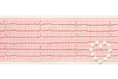 Сердце сделанное из белых таблеток формы сердца на бумажном ECG приводит к Стоковое Изображение RF
