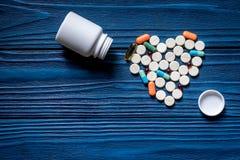 Сердце сделанное из пилюлек и бутылки пилюльки на голубом copyspace взгляд сверху предпосылки деревянного стола Стоковое фото RF