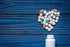 Сердце сделанное из пилюлек и бутылки пилюльки на голубом copyspace взгляд сверху предпосылки деревянного стола Стоковая Фотография