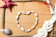 Сердце сделанное seashells с границей веревочек и узлов на досках Стоковые Фотографии RF