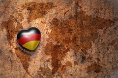 Сердце с национальным флагом Германии на винтажной предпосылке бумаги отказа карты мира Стоковое фото RF