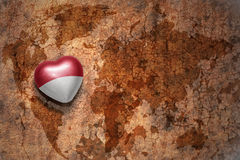 Сердце с национальным флагом Индонезии на винтажной предпосылке бумаги отказа карты мира стоковое фото rf