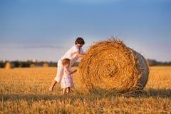 Сестра брата и младенца нажимая связки сена в поле Стоковое Фото