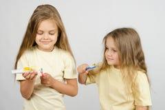 Сестра девушки наблюдая сжимая зубную пасту на щетке Стоковые Фото