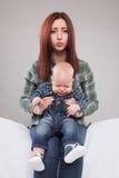 Сестра держа ее плача брата младенца стоковое фото rf