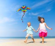 Сестра и брат играя с змеем на пляже Стоковые Фото